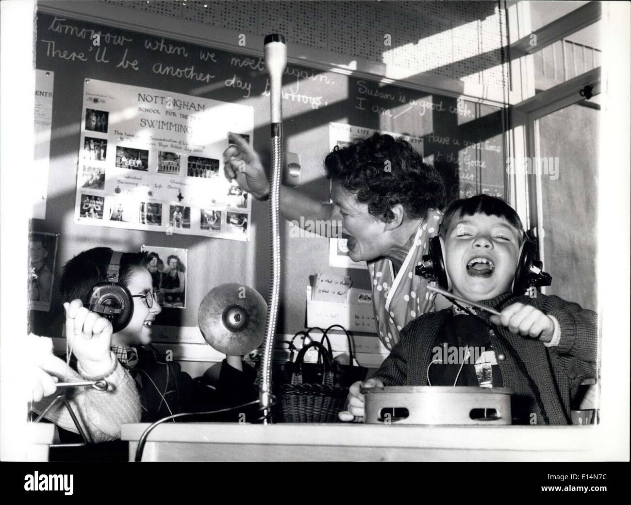 Apr. 05, 2012 - ''There'll Be Another Day tomorrow....'' and when it comes these deaf children will still be as happy as they are right now during a music lesson when the sounds of a record are transmitted to their ears via headphones. With them is teacher Dorothy Marriott. On right is our friend Anita Taylor, eight. - Stock Image