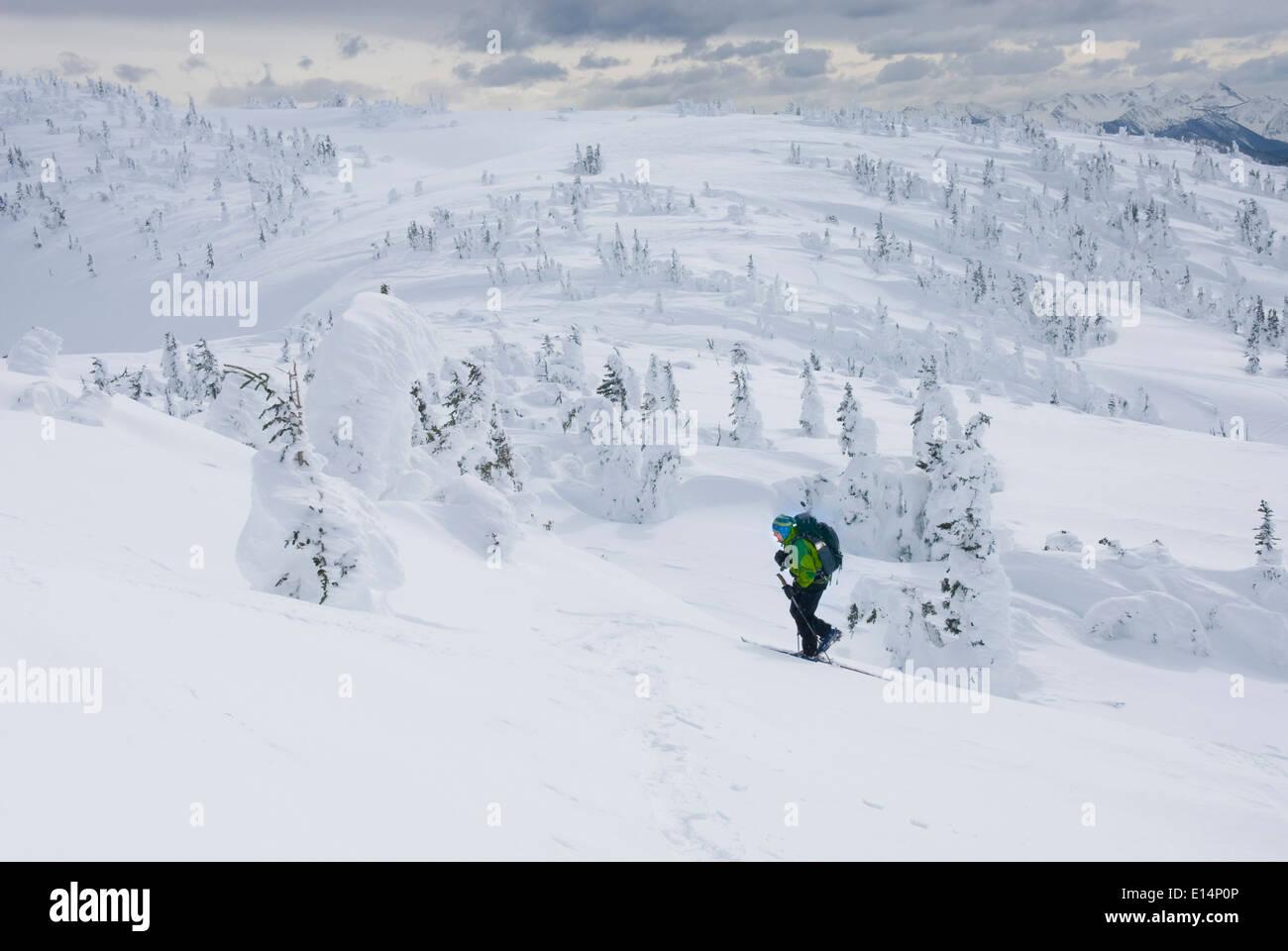 Caucasian snowshoer walking up snowy hillside - Stock Image