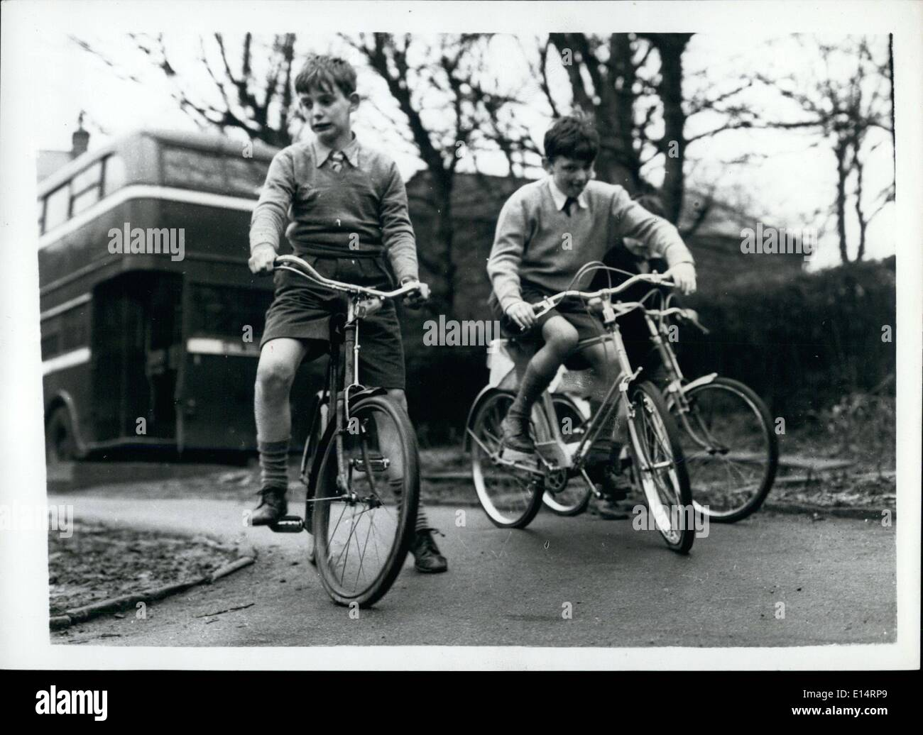 Apr. 18, 2012 - Riding Bikes. and they are blind. looks of grim determination on their faces as they ride their bikes. The school bus they play on is seen in the background. - Stock Image