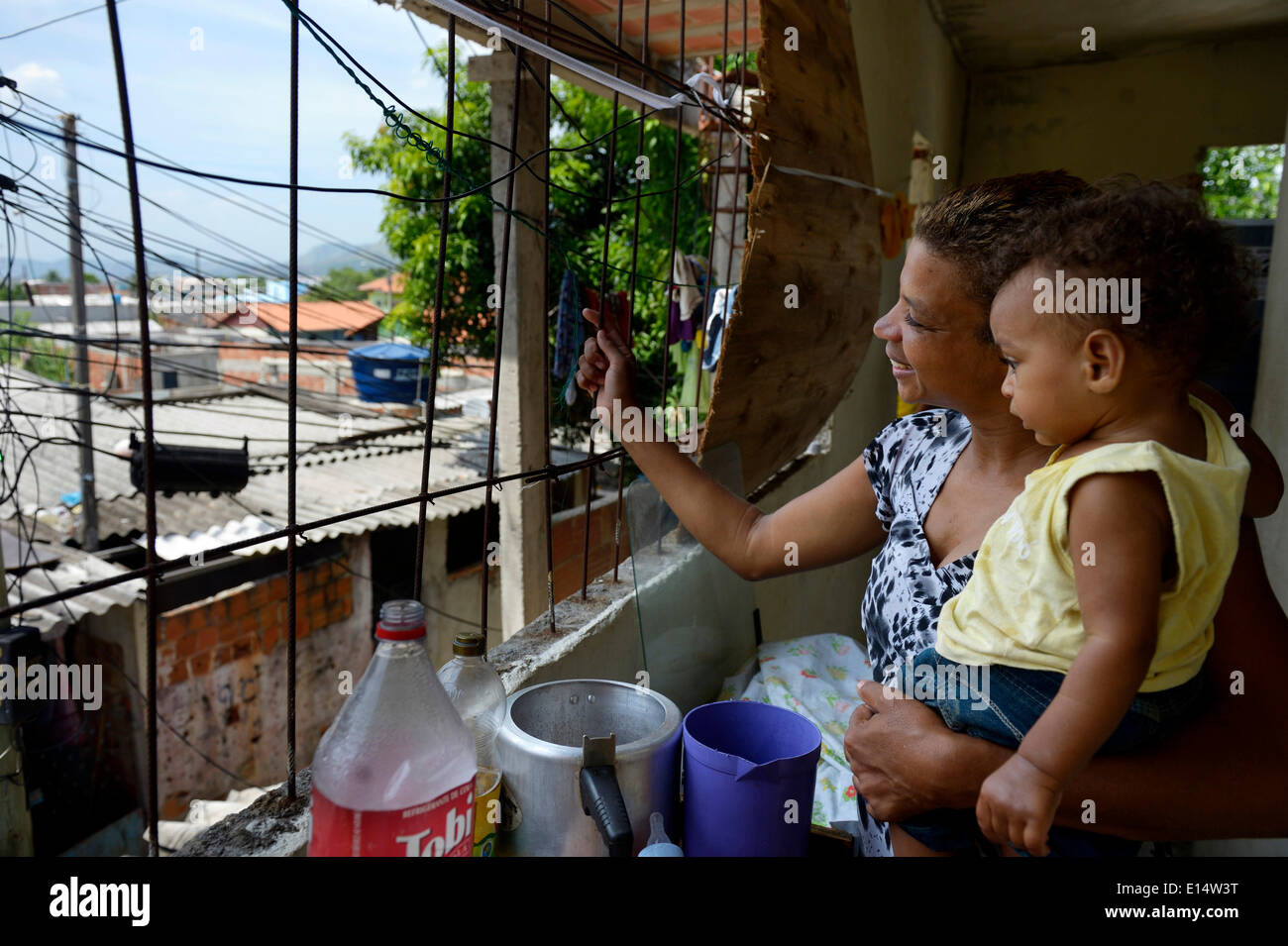 Woman, 38, with her son, 1 year, looking out the window of her house in the Senador Camara favela, Rio de Janeiro - Stock Image