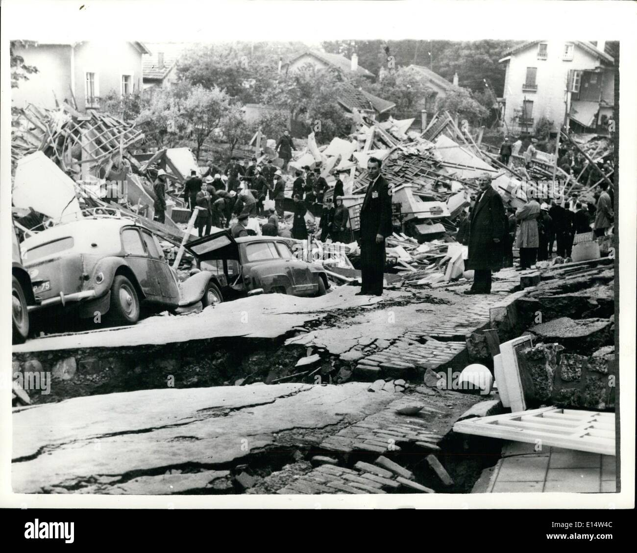 Apr. 18, 2012 - Seven killed In Landslide In Paris Suburb. Seven people were killed and 23 injured when half a square mile of the Paris suburb of Clamart subsided this morning, smashing 25 houses, a ceramics factory and a three-storey block of flats. About a dozen workers are believed to be buried alive in the factory ruins. Keystone Photo Shows:- Cars are seen on a collapsed roadway as rescue workers toil among the wreckage in the background - after today's disaster at Clamart. - Stock Image