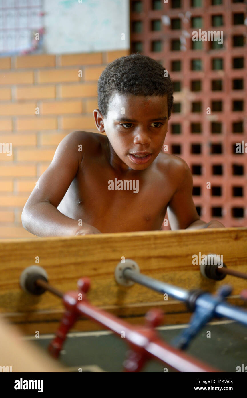Boy, 9, playing table football, Sao Martinho social project for street children, Lapa district, Rio de Janeiro - Stock Image