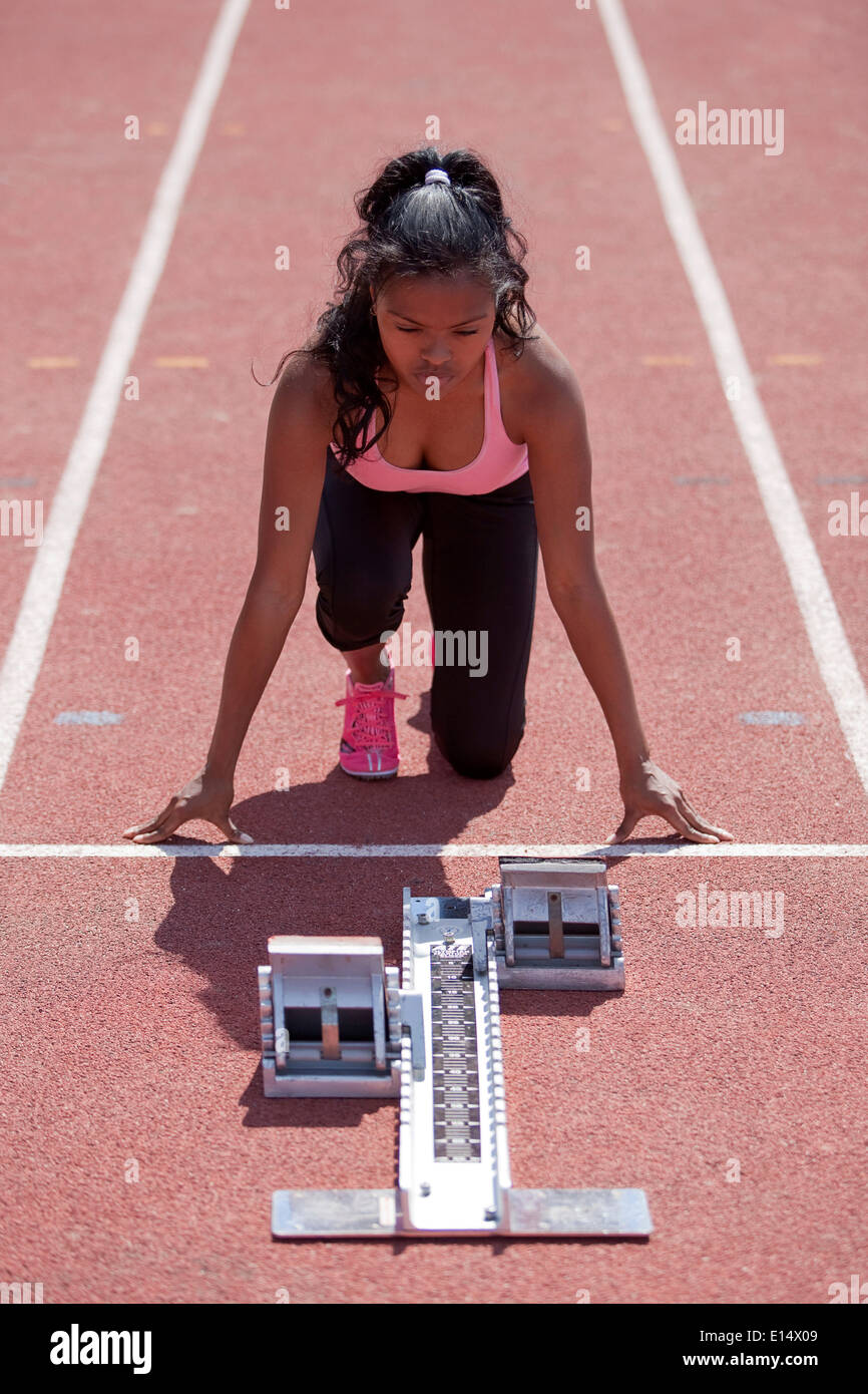 Sporty young woman getting ready on running track, starting block Stock Photo