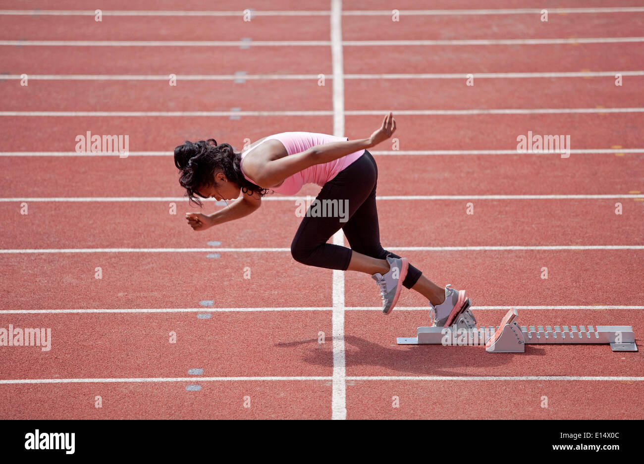 Sporty young woman starting from starting block to run on running track Stock Photo