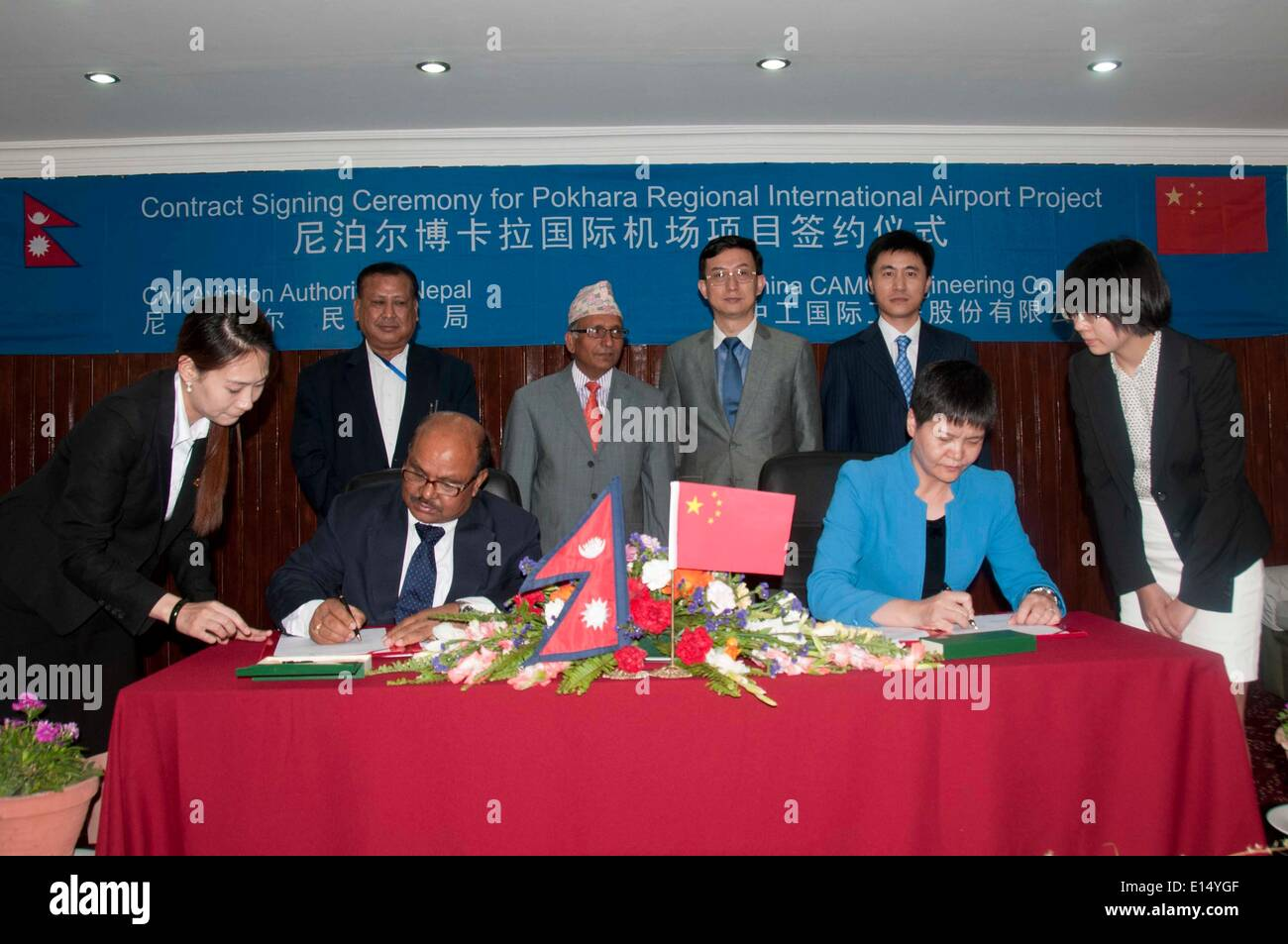 Kathmandu, Nepal. 22nd May, 2014. Ratish Chandra Lal Suman (2nd L front), chief of Civil Aviation Authority of Nepal (CAAN), the aviation regulatory body in the country, and Luo Yan (2nd R front), chairman and president of China CAMC Engineering Co., sign a construction agreement for the Pokhara Regional International Airport in Kathmandu, Nepal, May 22, 2014. The Nepal government has on Thursday signed a construction agreement with China CAMC Engineering Co. for the development of the second international airport in the country. © Pratap Thapa/Xinhua/Alamy Live News - Stock Image