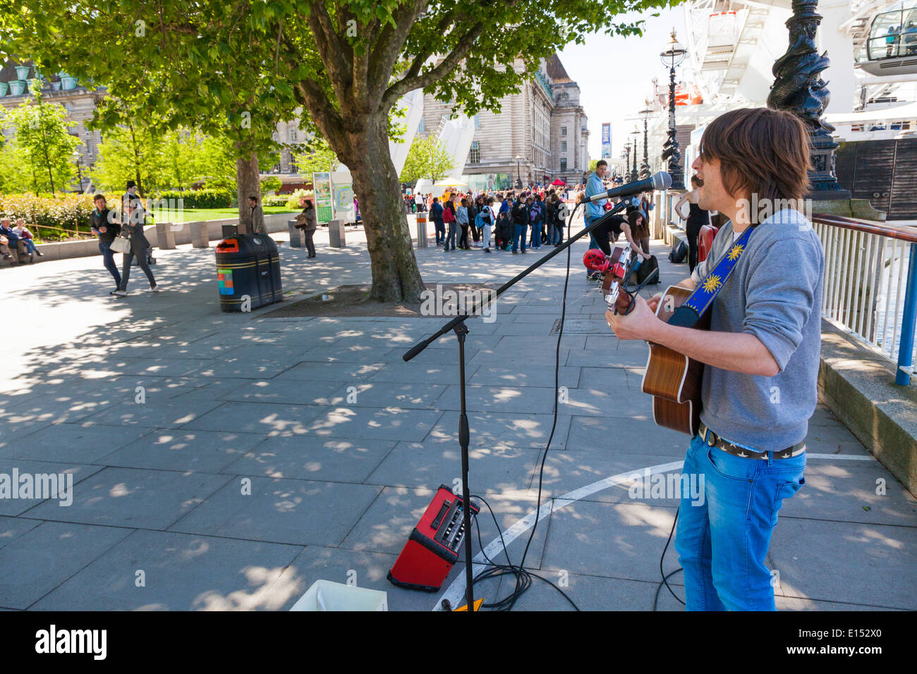 Busker playing acoustic guitar on the London embankment - Stock Image