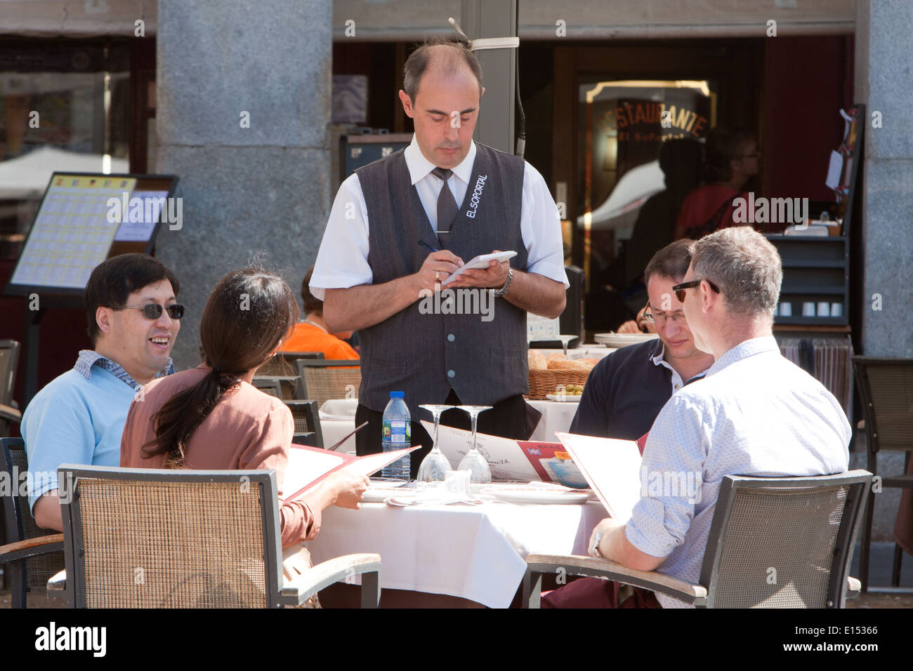 A waiter takes orders from diners at a restaurant in the Plaza Mayor - Stock Image