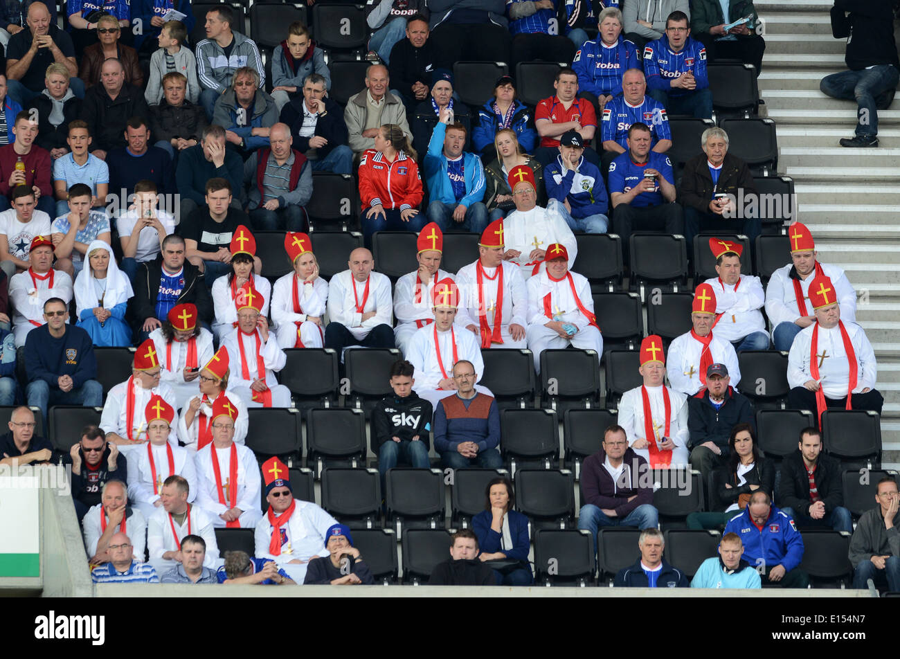 Carlisle United Football Club supporters fans dressed as priests in religious fancy dress costumes as they watch get relegated - Stock Image