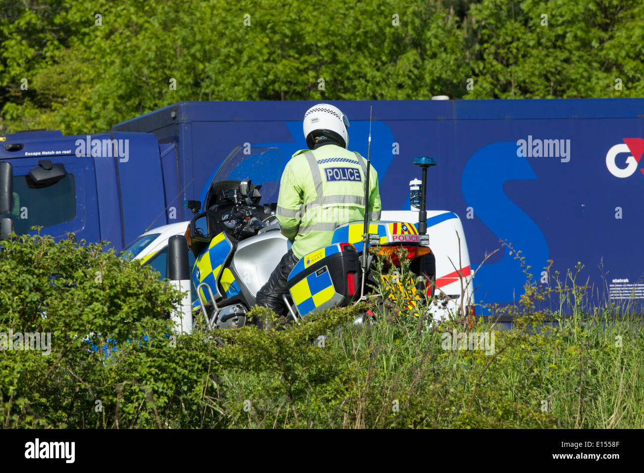 Police motorcycle in layby on Dual Carriageway with G4S van passing - Stock Image