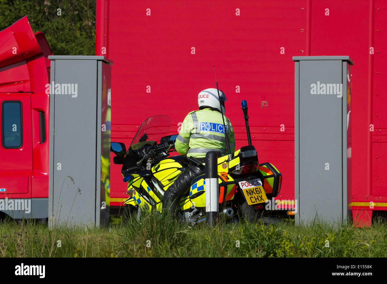 Police motorcycle in layby on Dual Carriageway with Royal Mail truck passing - Stock Image
