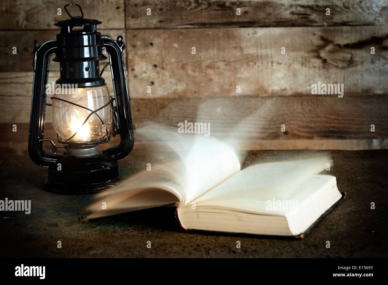 Old book and kerosene lamp on table - Stock Image