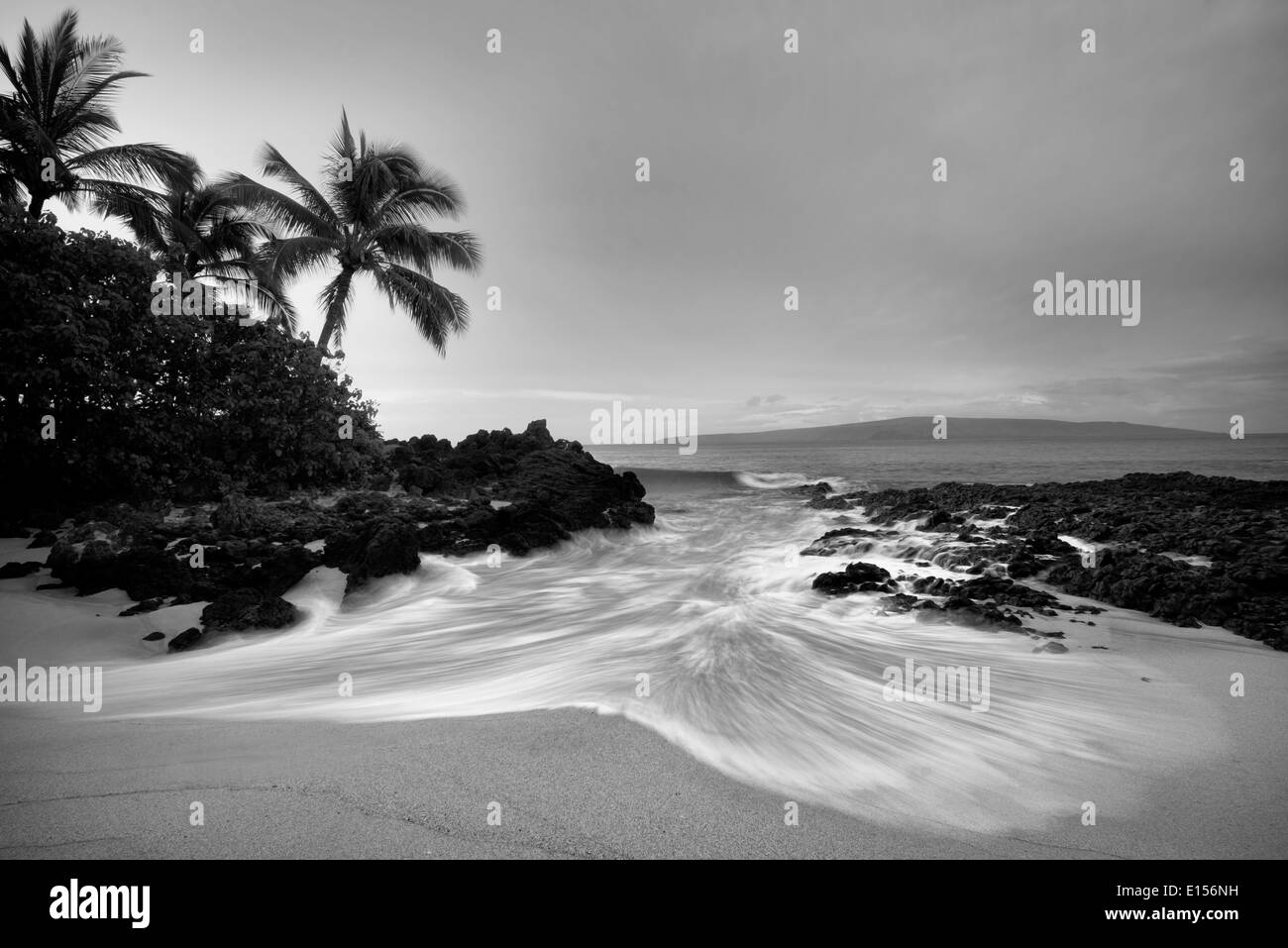 Secluded beach with palm trees and sunrise. Maui, Hawaii - Stock Image