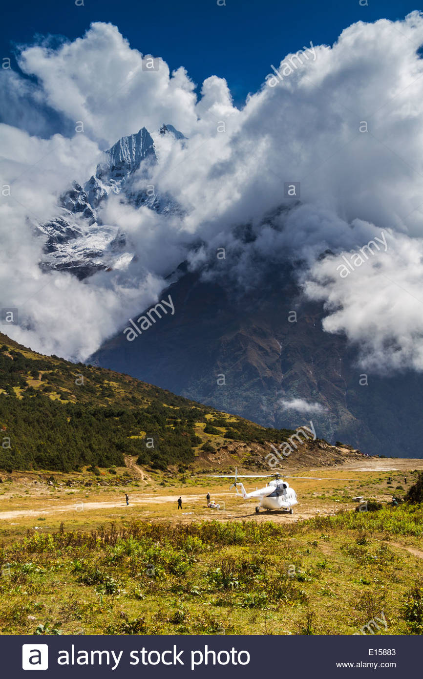 Sherpas Stand Around Cargo Offloaded From A Helicopter At A High Altitude Airstrip Near Mount Everest, Nepal - Stock Image