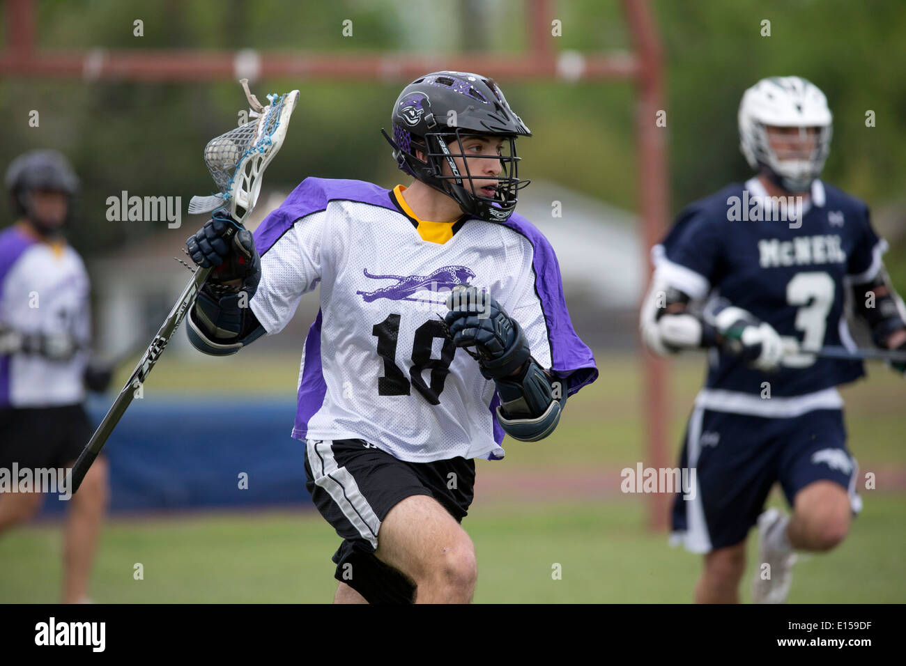Texas high school boy's lacrosse action featuring LBJ High School (purple) vs. Round Rock McNeil (dark blue). - Stock Image