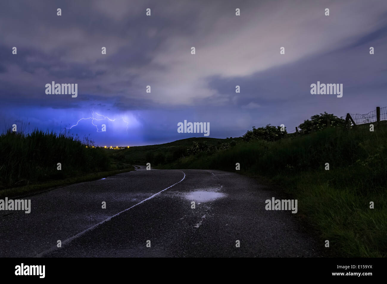 A road leads to a storm raging behind the hills. Stock Photo