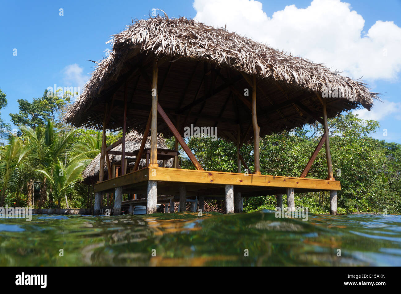 Thatched hut on stilts viewed from the sea surface - Stock Image