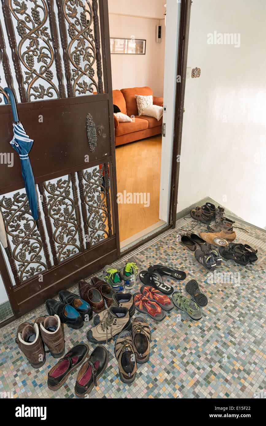 China, Hong Kong, taken off shoes of guests in front of an entrance door in a house corridor - Stock Image
