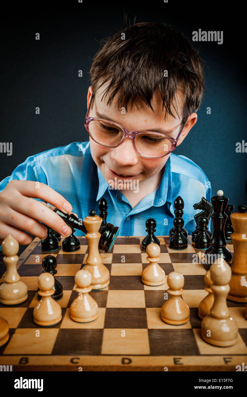 Wunderkind play chess. Funny Nerd boy. - Stock Image