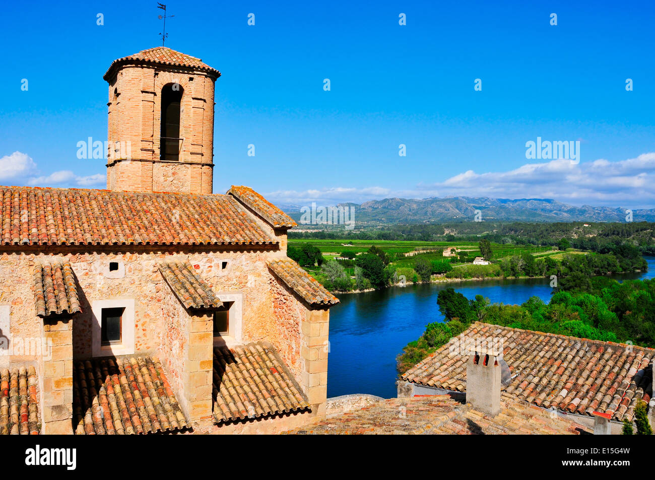 Esglesia Vella Church and Ebro River in Miravet, Spain with the Serra de Cardo mountain range in the background - Stock Image