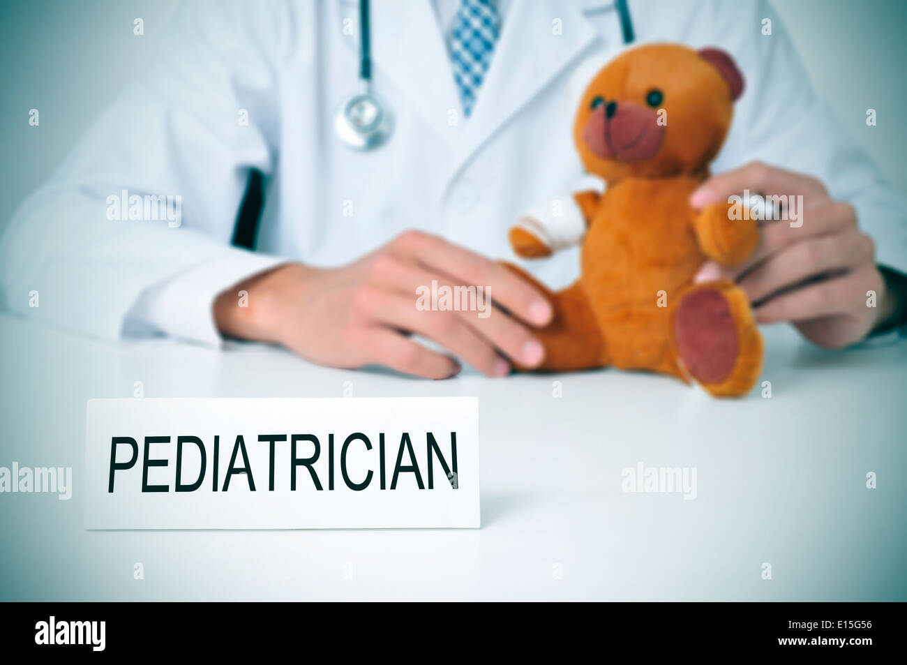 a doctor sitting in a desk with a injured teddy bear and a nameplate with the word pediatrician written in it - Stock Image