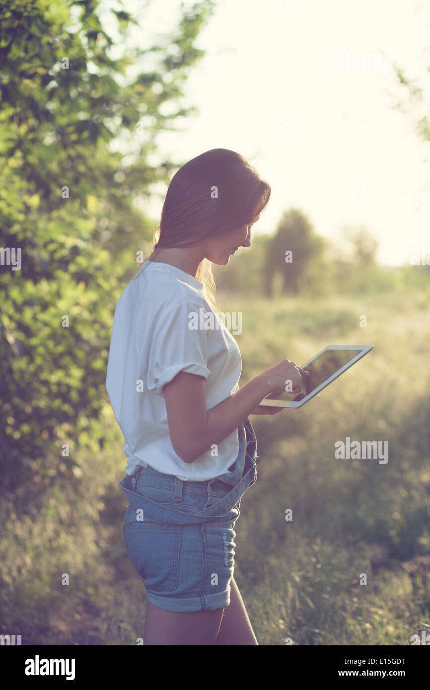 trendy girl using a tablet pc outdoors - Stock Image