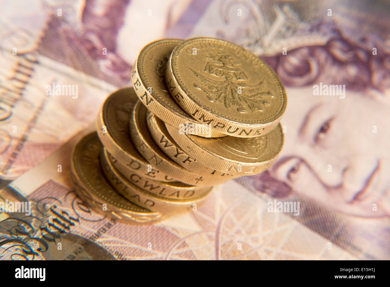 a pile of pound coins and some twenty pound notes Stock Photo