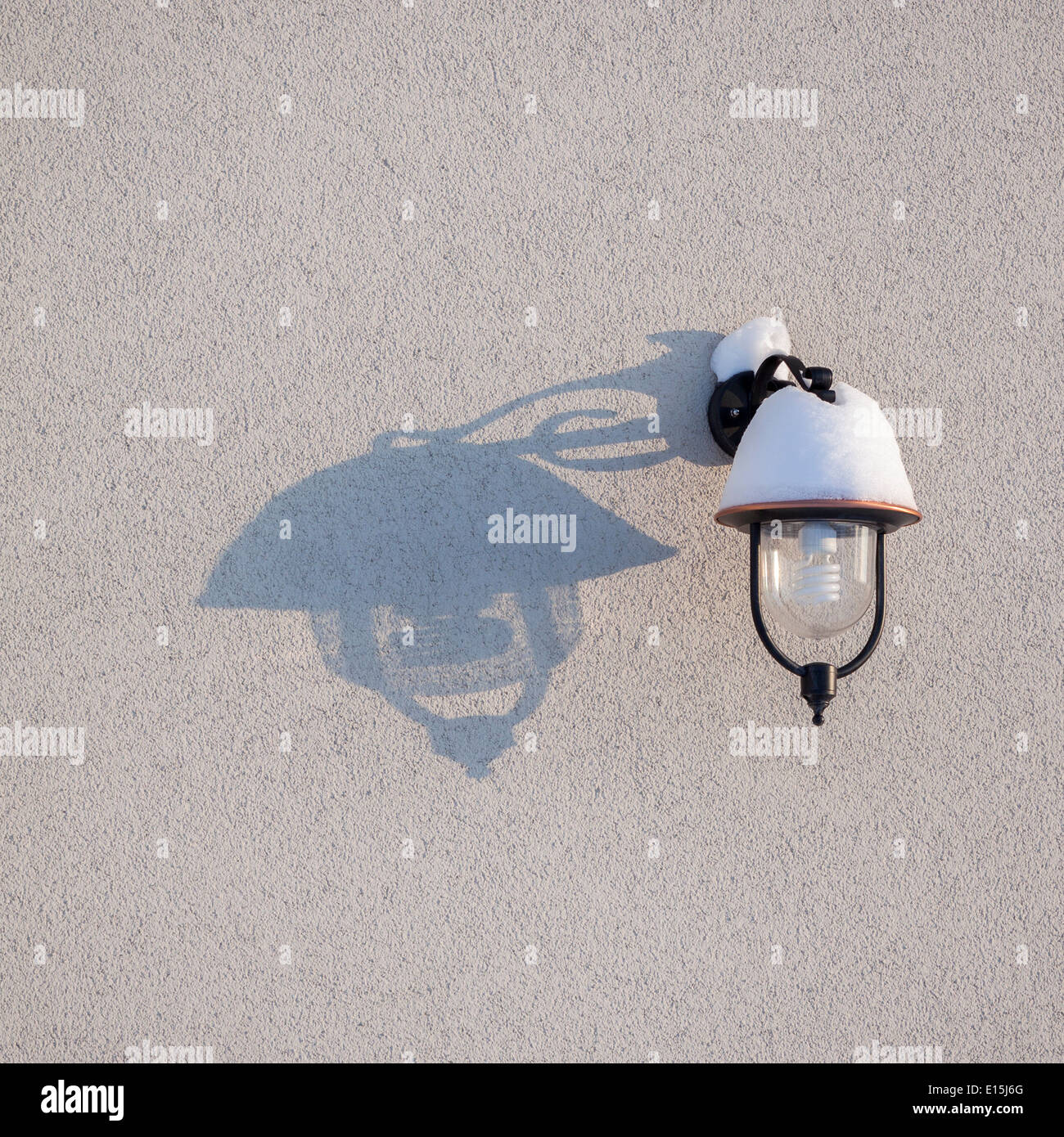 Outdoor lamp covered with snow and its shadow on the wall - Stock Image