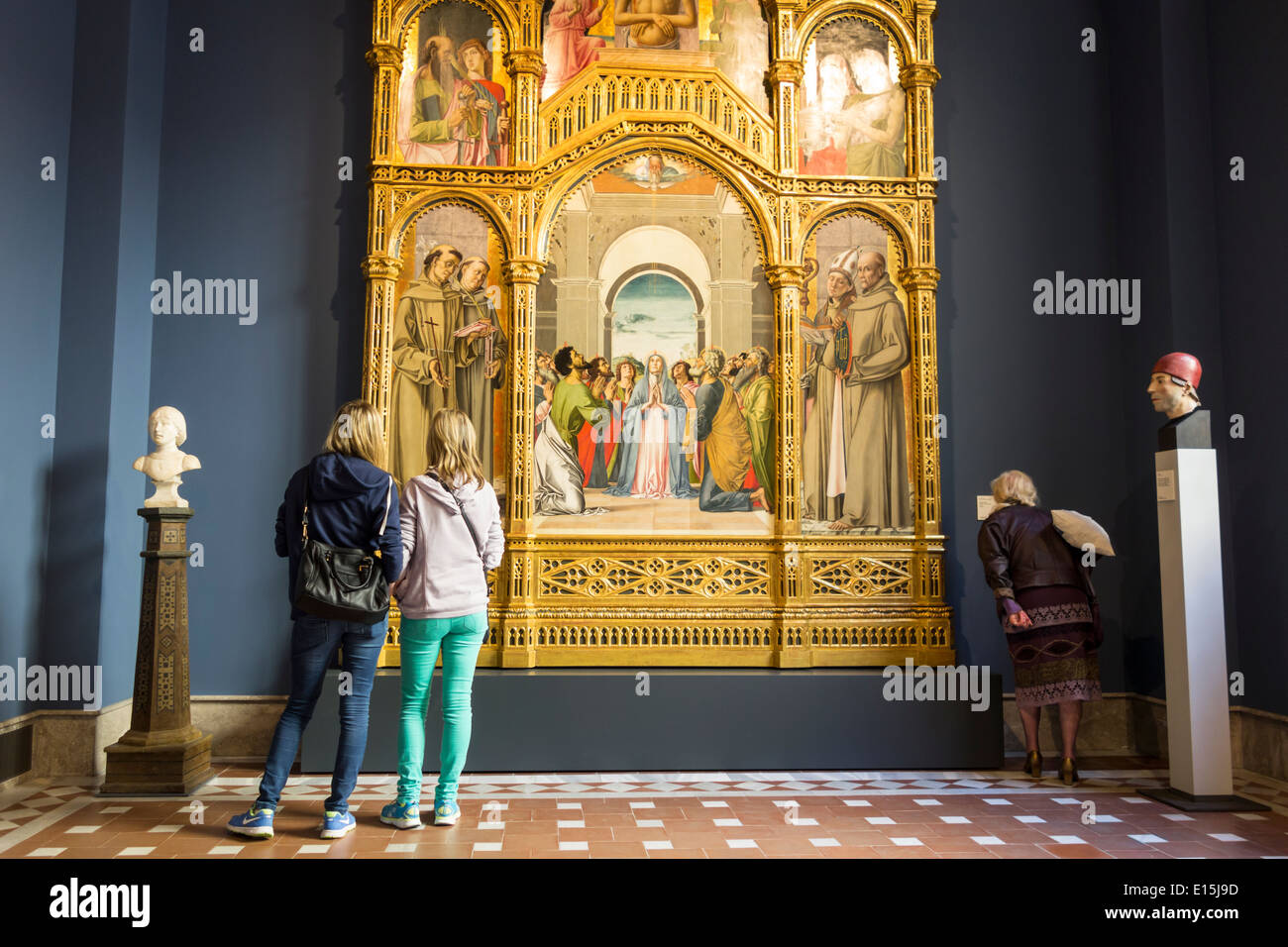 Two young girls and an older woman contemplating a painting in Bode museum in Berlin, Germany - Stock Image