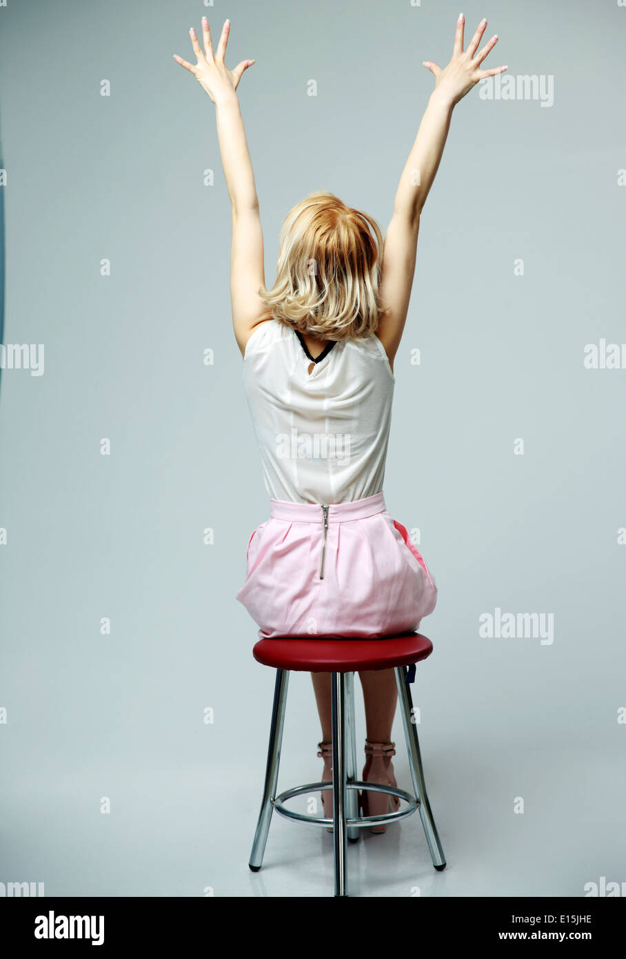 back view portrait of a young woman sitting with hands raised up on gray background - Stock Image