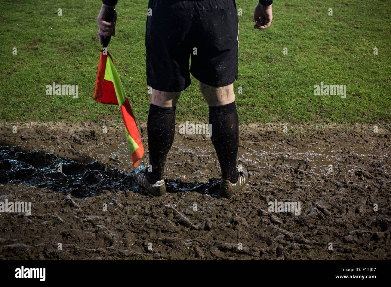 A referee's assistant's legs covered in mud during Belper Town FC's match against Gresley, Belper, Derbyshire. - Stock Image