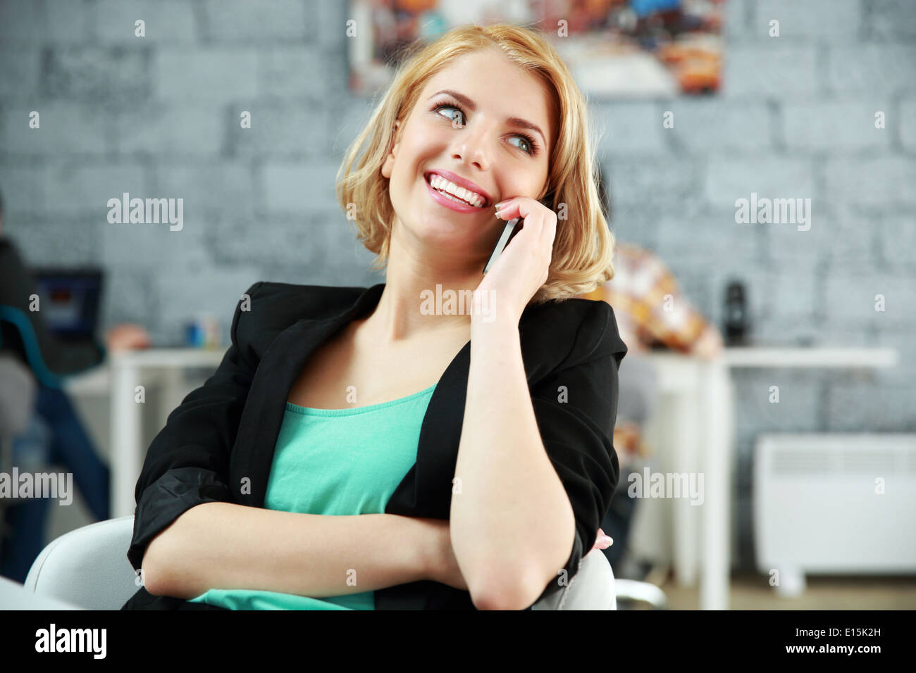 Young happy woman talking on the phone at office - Stock Image