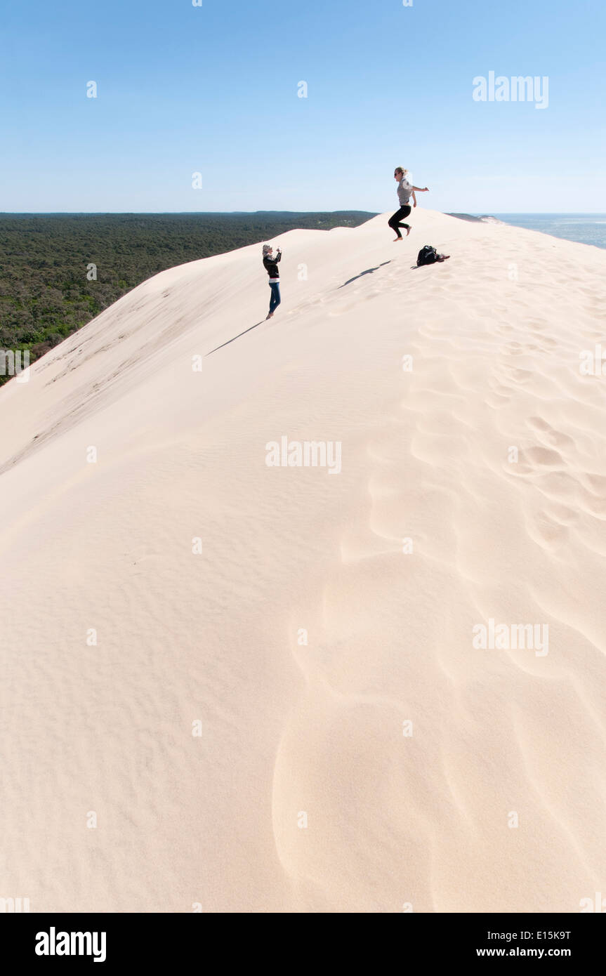 France, Gironde, Bassin d'Arcachon (Arcachon Bay). Teenager taking a photograph of a friend jumping on the Dune of Pyla - Stock Image
