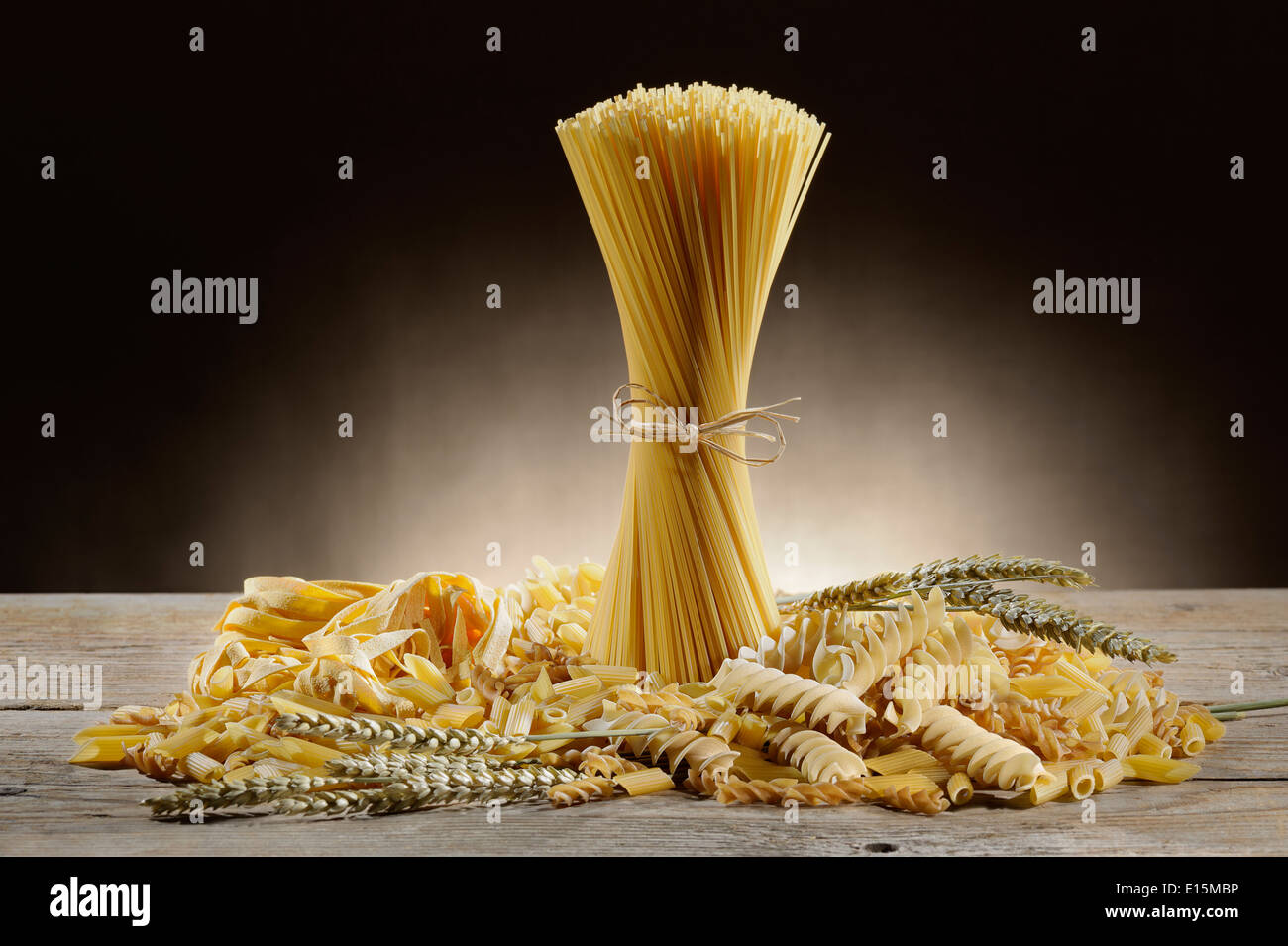 variety of uncooked pasta on wooden table with ears of wheat Stock Photo