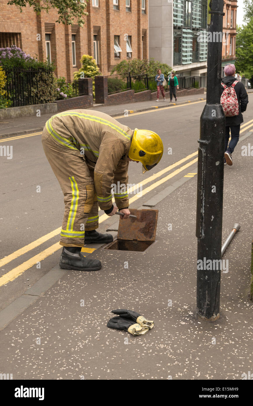 Strathclyde Fire and Rescue Officer opening a Fire Hydrant cover to access water, Glasgow, Scotland, UK - Stock Image