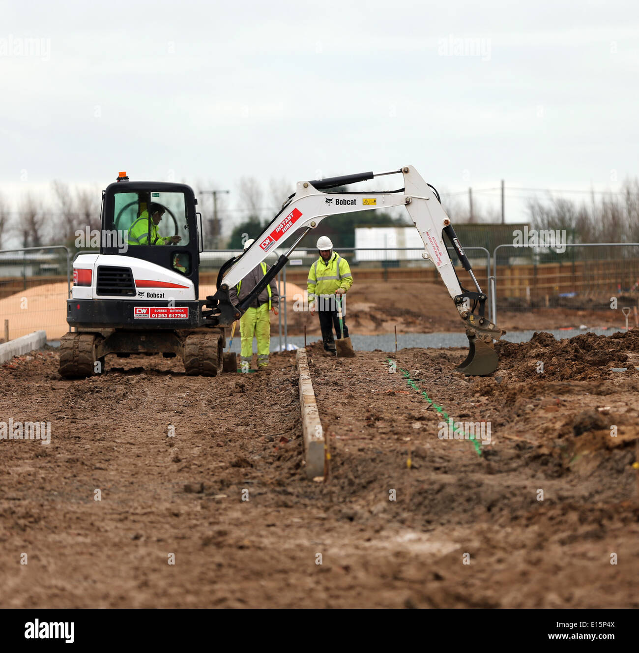 Tradesman workman on a building site in a digger excavating groundwork - Stock Image