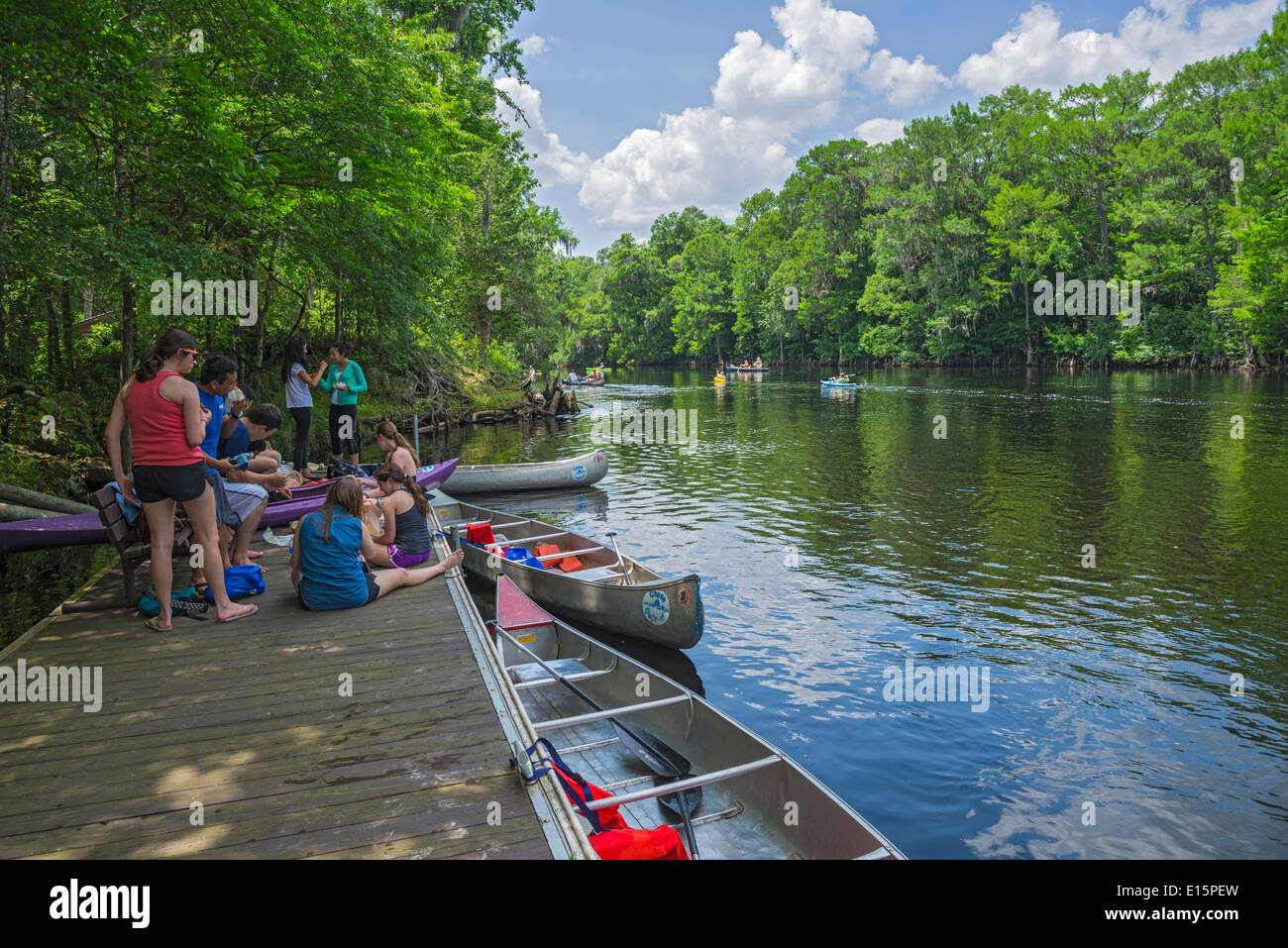Young canoers stop for lunch along the Santa Fe River at a floating dock near Poe Springs Park in High Springs, Florida. - Stock Image