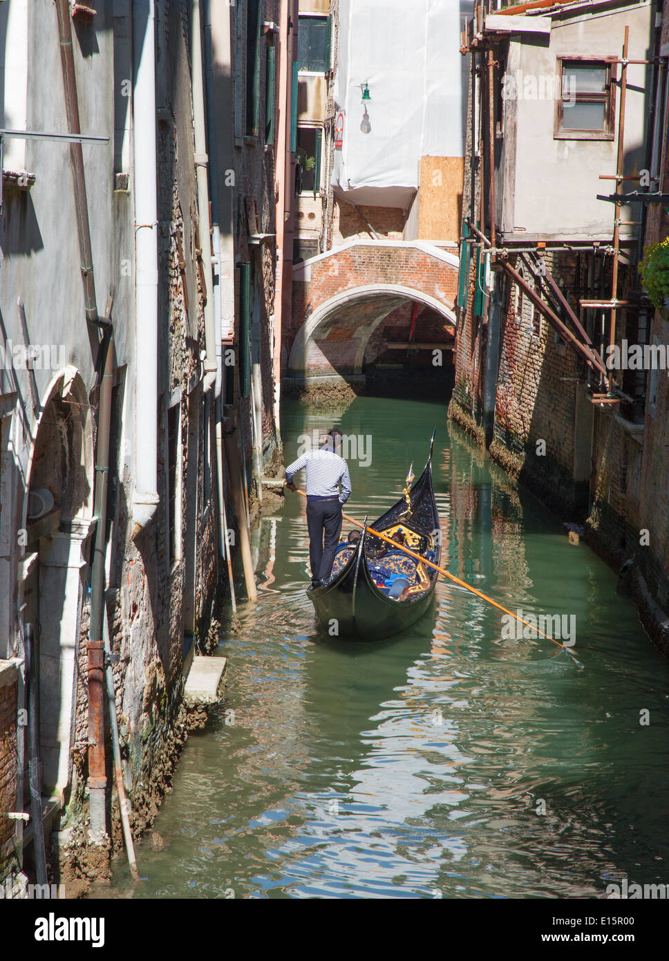 VENICE, ITALY - MARCH 12, 2014: Gondolier on the little canal in center of the town. - Stock Image