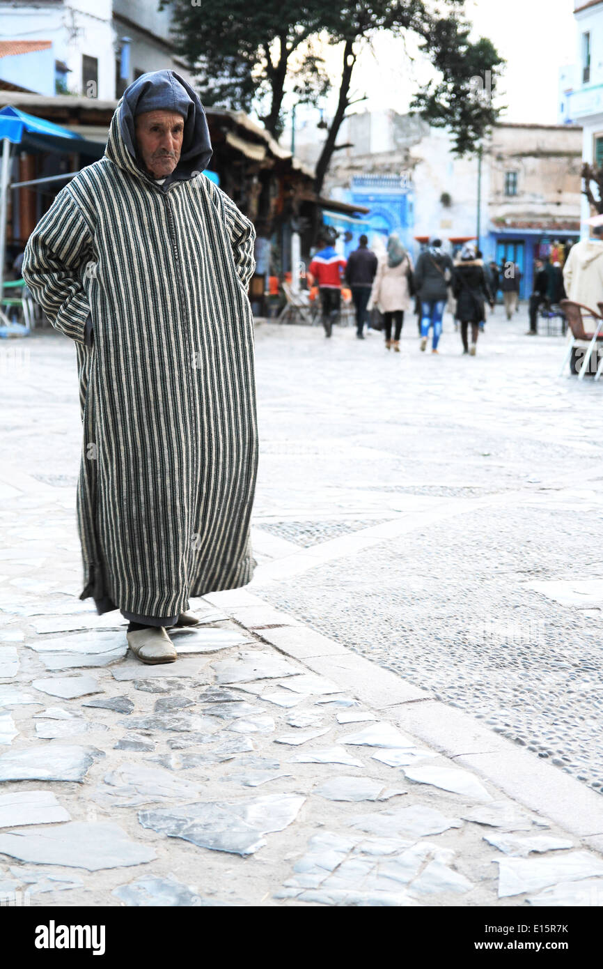 f96d759c05b960 Traditional Moroccan man wearing a Djellaba walking in the town of  Chefchaouen