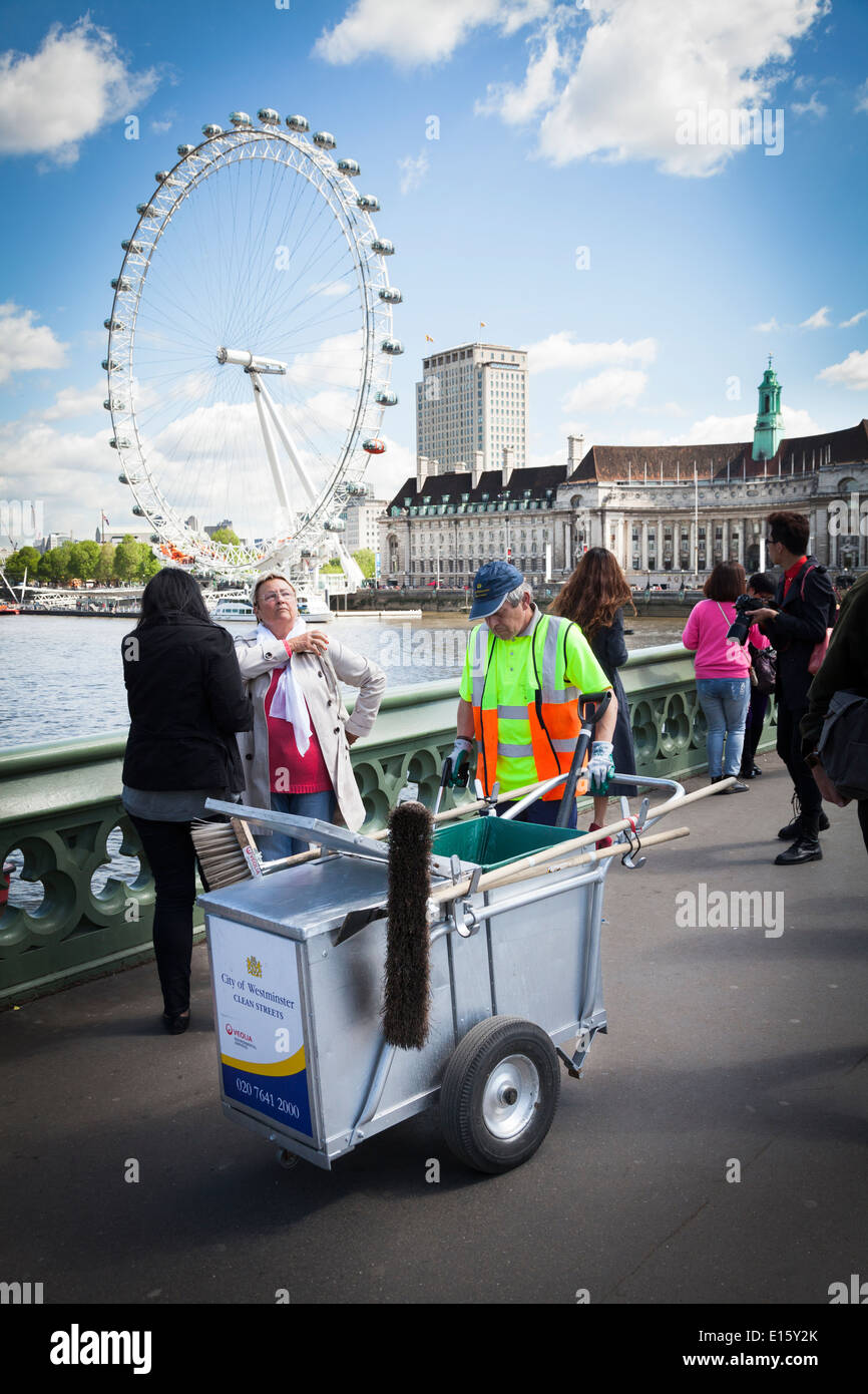 Street cleaner with cart amongst tourists with London Eye. - Stock Image
