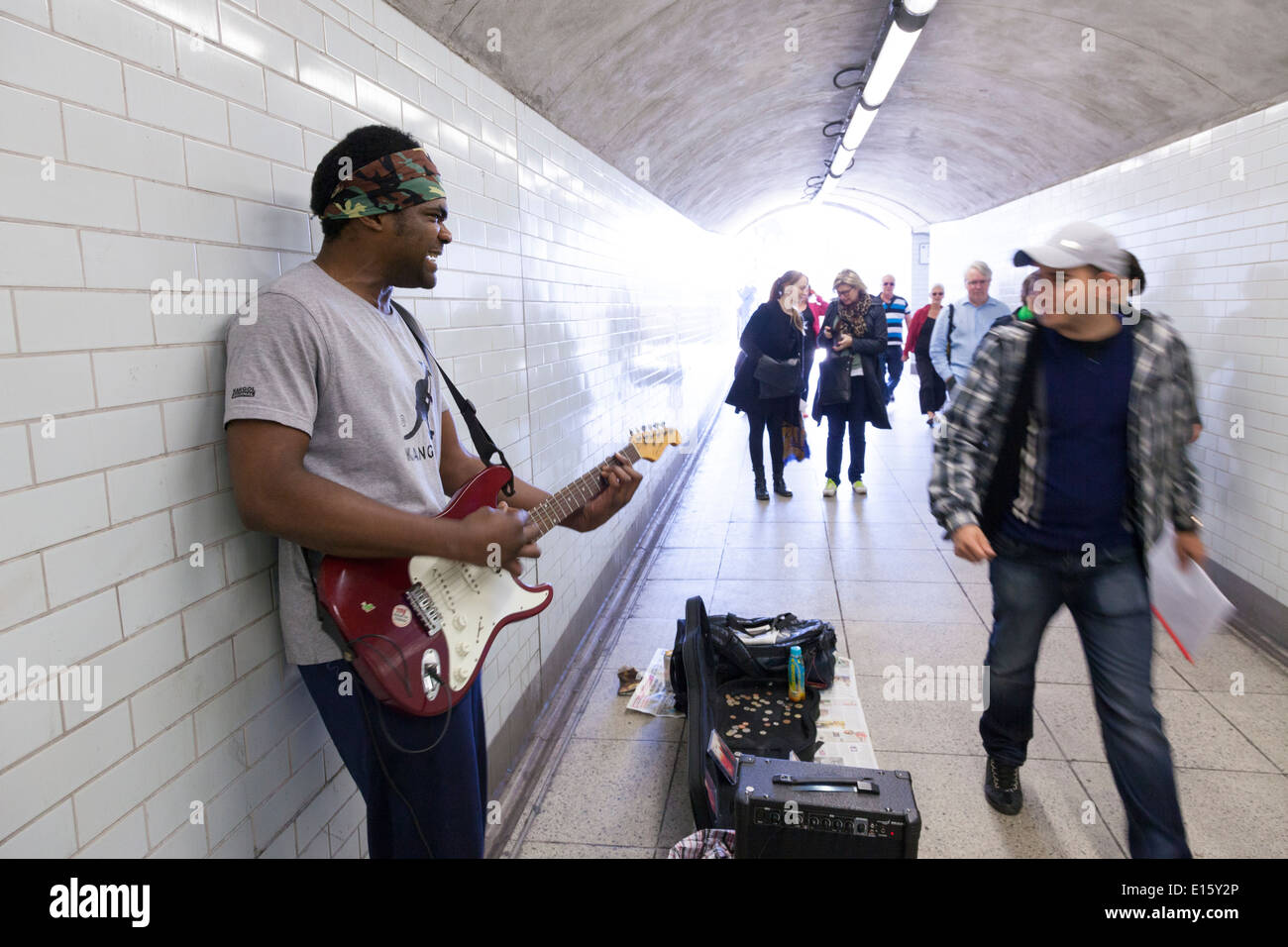 Busker playing electric guitar in underpass. - Stock Image