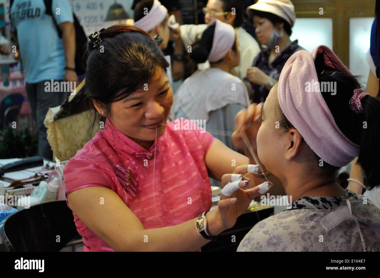 Face massage with string, Raohe Street Night Market, Taipei, Taiwan. - Stock Image
