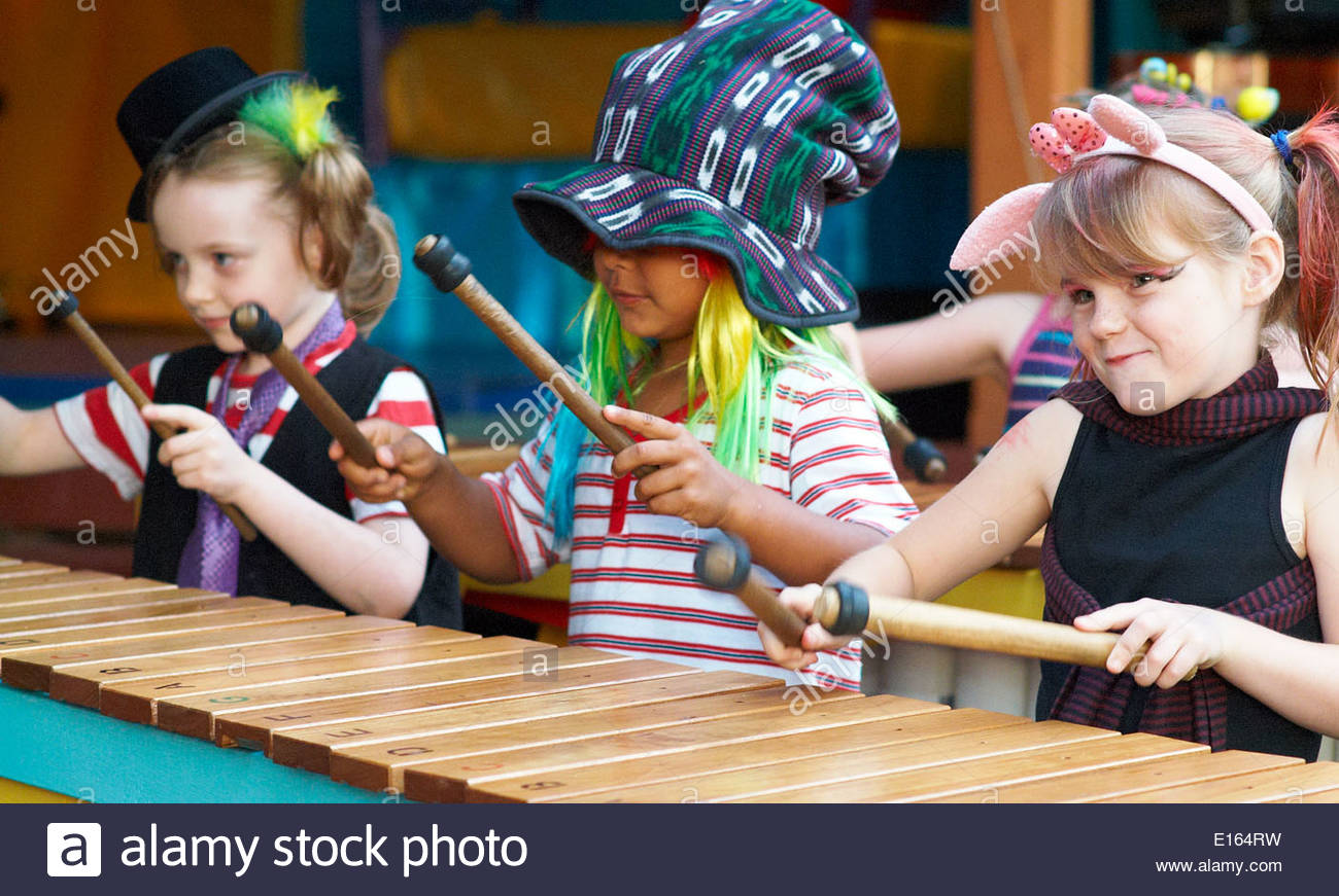 Primary school students - two girls and a boy - in colorful 'Dr Zeus style' fancy dress, playing the marimba at a school concert; in NSW, Australia. - Stock Image
