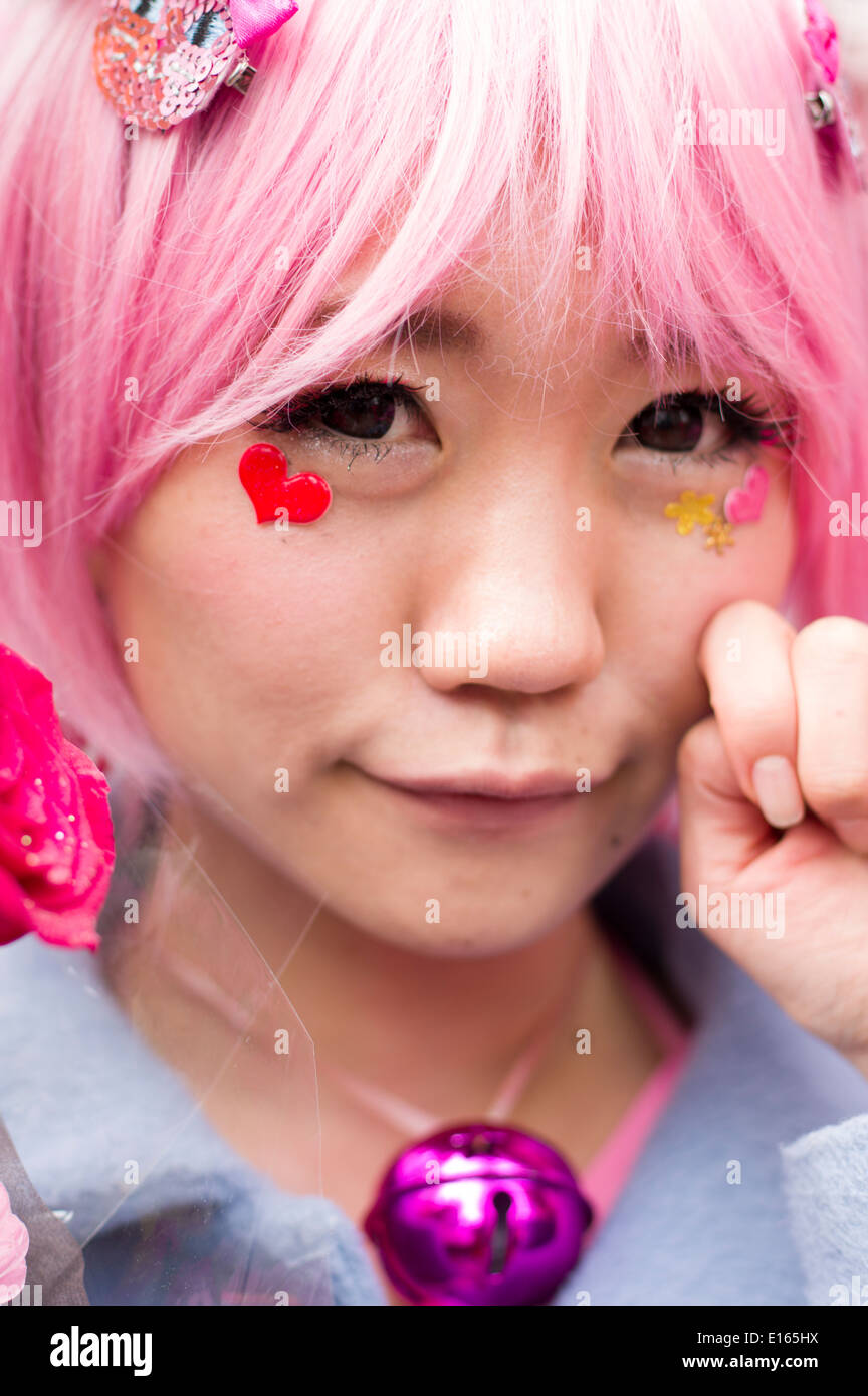 Japanese woman with pink hair and heart stickers on face. Kawaii culture. Tokyo, Japan - Stock Image