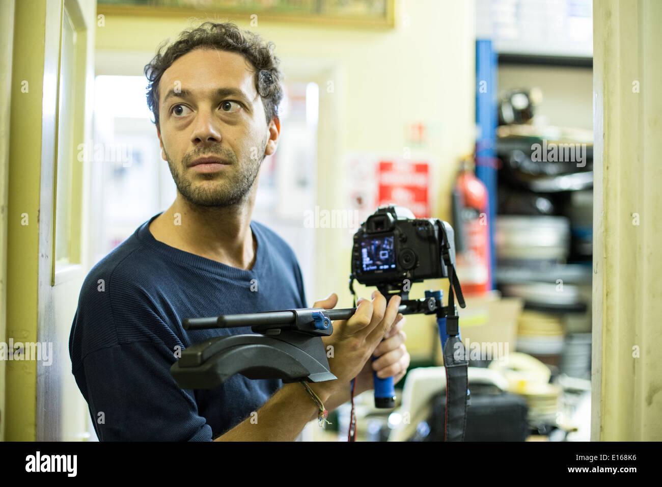 italian film maker filming footage on digital camera at tony scott's film lab in acton london - Stock Image