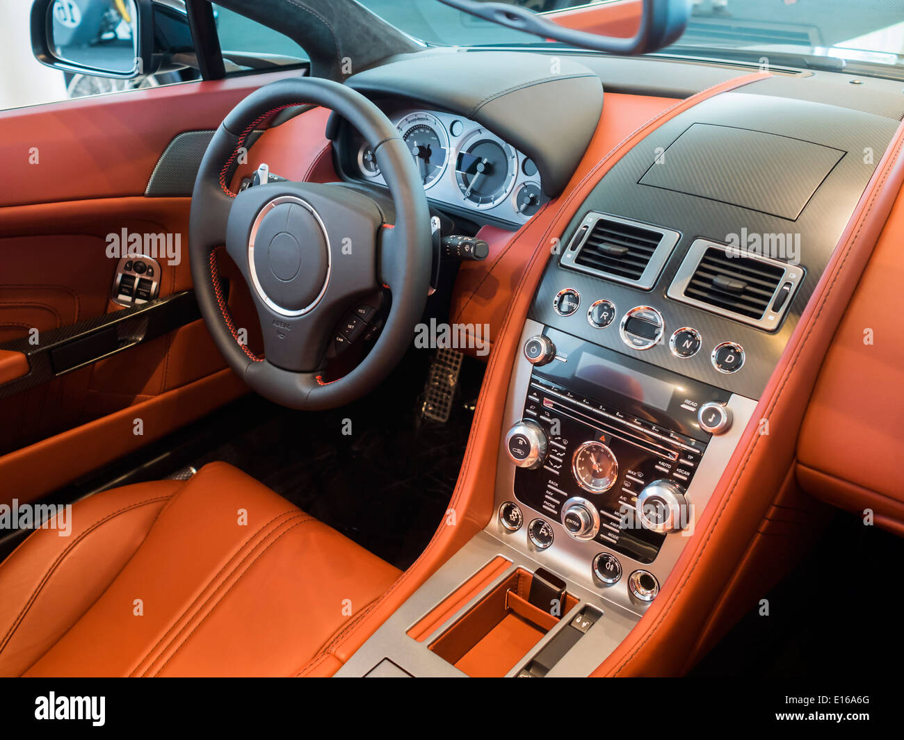 interior cockpit/dashboard of an expensive sports car lined in leather and carbon fiber. - Stock Image
