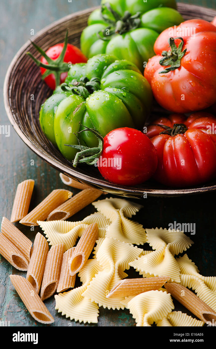 Fresh green and red tomatoes with mixed pasta - Stock Image