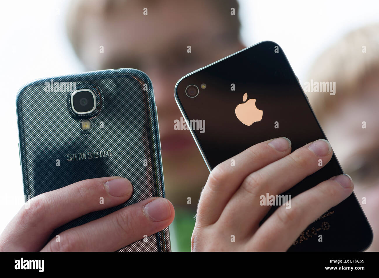 Two teenagers are posing with their Samsung Galaxy S4 (left) and iPhone 4 smartphones. - Stock Image