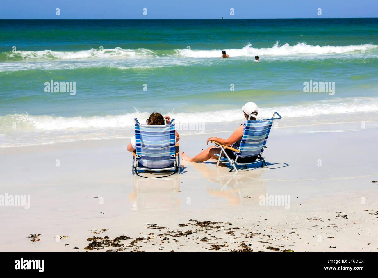 Two Women Enjoy Sitting In Beach Chairs On The Shoreline Of Siesta Key Beach  Florida