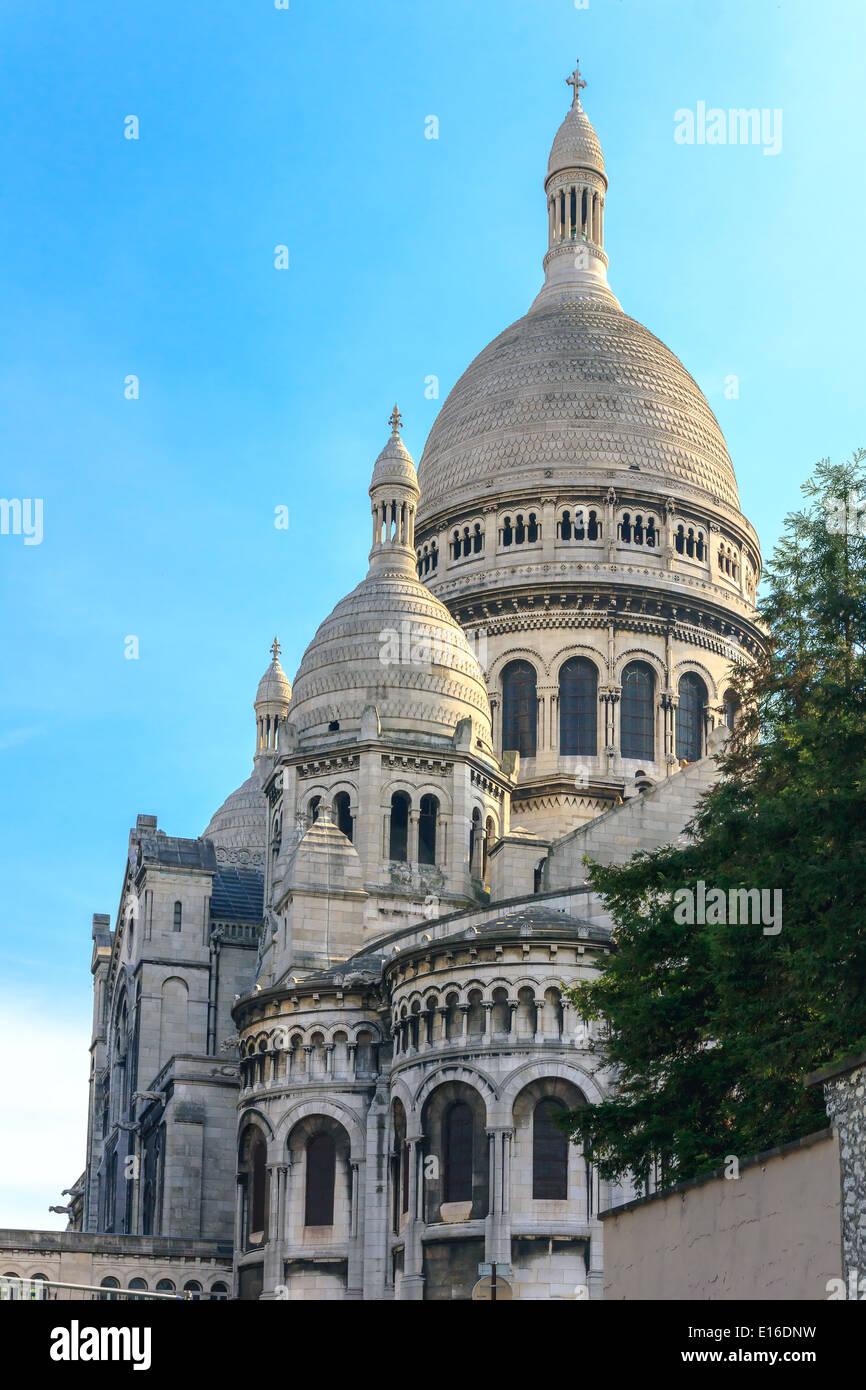 View of the Basilique du Sacré-Cœur (Basilica of the Sacred Heart of Jesus) at the butte Montmartre of Paris evening - Stock Image