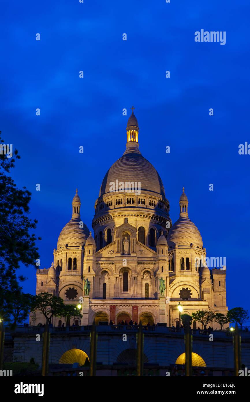 View of the Basilique du Sacré-Cœur (Basilica of the Sacred Heart of Jesus) at the butte Montmartre of Paris at night - Stock Image